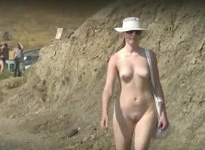 Naturist damsel ambles on the beach..